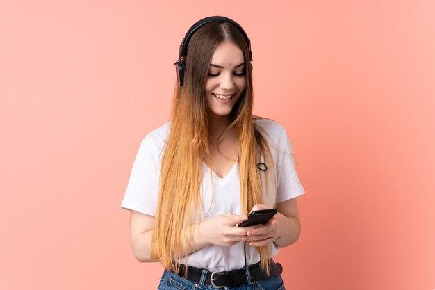 Jovem mulher caucasiana isolada na parede rosa, ouvindo música e olhando para o celular Foto Premium