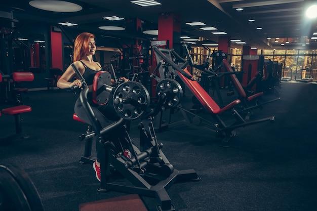 Jovem mulher caucasiana muscular praticando na academia com equipamento. bem-estar, estilo de vida saudável, musculação. Foto gratuita