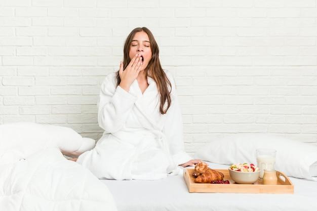 Jovem mulher caucasiana na cama bocejando mostrando um gesto cansado, cobrindo a boca com a mão. Foto Premium