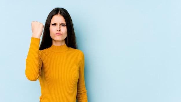 Jovem mulher caucasiana na parede azul, mostrando com uma expressão facial agressiva. Foto Premium