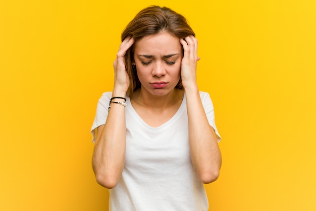 Jovem mulher caucasiana natural tocando seus templos e tendo dor de cabeça. Foto Premium