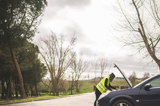 Jovem mulher caucasiana, olhando para o motor do carro, carro quebrado no meio da estrada. conceito de assistência automóvel e na estrada. Foto Premium
