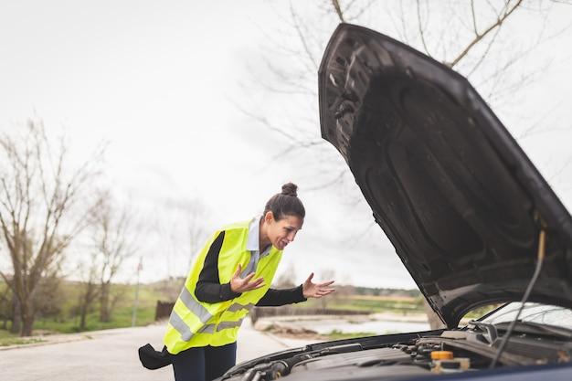Jovem mulher caucasiana, olhando para o motor do carro, ela não sabe o que fazer, carro quebrado no meio da estrada. conceito de assistência automóvel e na estrada. Foto Premium
