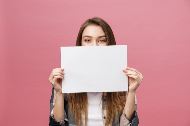 Jovem mulher caucasiana, segurando a folha de papel em branco Foto Premium