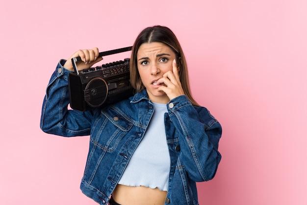 Jovem mulher caucasiana, segurando as unhas roer um guetto, nervoso e muito ansioso. Foto Premium