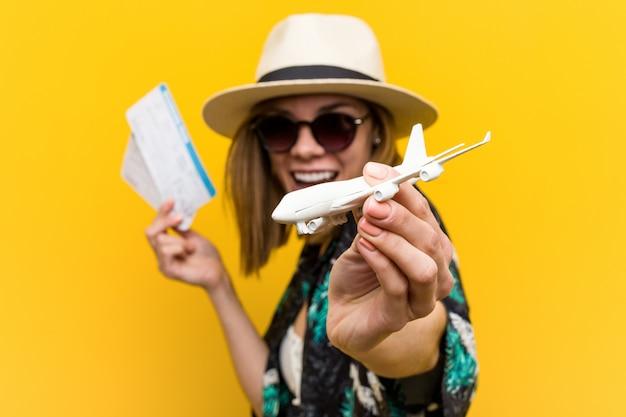 Jovem mulher caucasiana segurando bilhetes de avião muito feliz Foto Premium