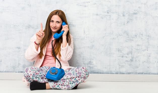 Jovem mulher caucasiana, segurando o telefone fixo, mostrando o número um com o dedo. Foto Premium