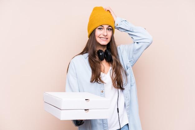 Jovem mulher caucasiana segurando pizzas isoladas sendo chocado, lembrou-se de uma reunião importante. Foto Premium