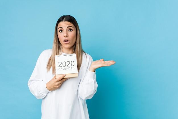 Jovem mulher caucasiana, segurando um calendário 2020 impressionado Foto Premium