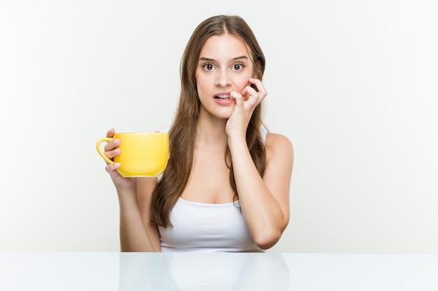 Jovem mulher caucasiana, segurando um copo de roer as unhas, nervoso e muito ansioso. Foto Premium