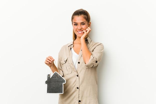 Jovem mulher caucasiana, segurando um ícone de casa, roer unhas, nervosas e muito ansiosas. Foto Premium