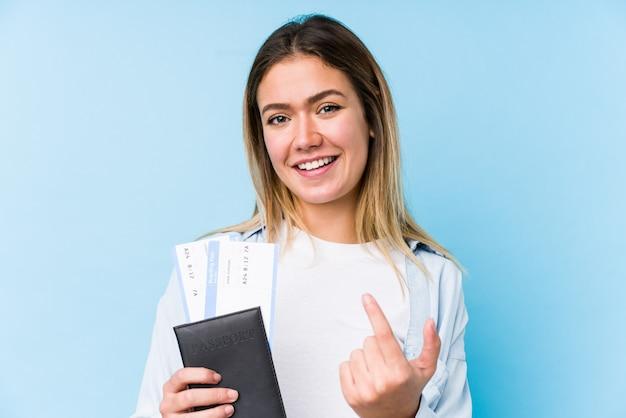 Jovem mulher caucasiana, segurando um passaporte isolado apontando com o dedo para você, como se convidando se aproximar. Foto Premium