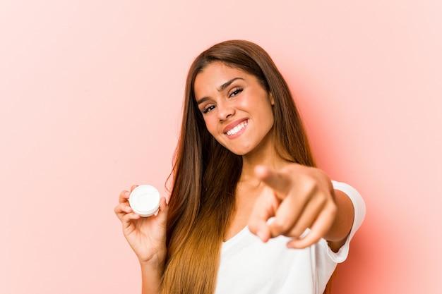 Jovem mulher caucasiana, segurando um sorriso hidratante alegre apontando para a frente. Foto Premium