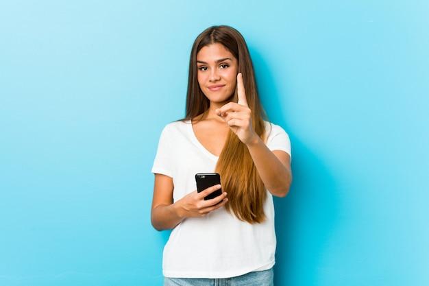 Jovem mulher caucasiana, segurando um telefone, mostrando o número um com o dedo. Foto Premium