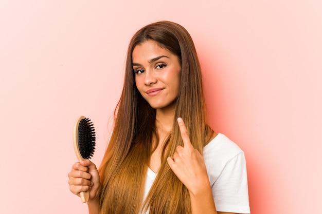 Jovem mulher caucasiana segurando uma escova de cabelo apontando com o dedo para você como se fosse um convite para se aproximar. Foto Premium