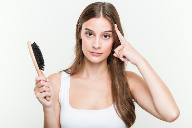 Jovem mulher caucasiana, segurando uma escova de cabelo, apontando seu templo com o dedo, pensando, focado em uma tarefa. Foto Premium