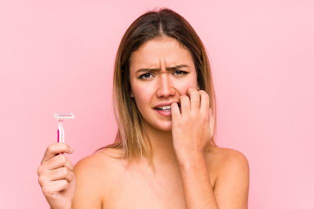 Jovem mulher caucasiana segurando uma lâmina de barbear isolada jovem mulher caucasiana segurando uma escova de cabelo isolada roer unhas, nervosa e muito ansiosa. <mixto> Foto Premium