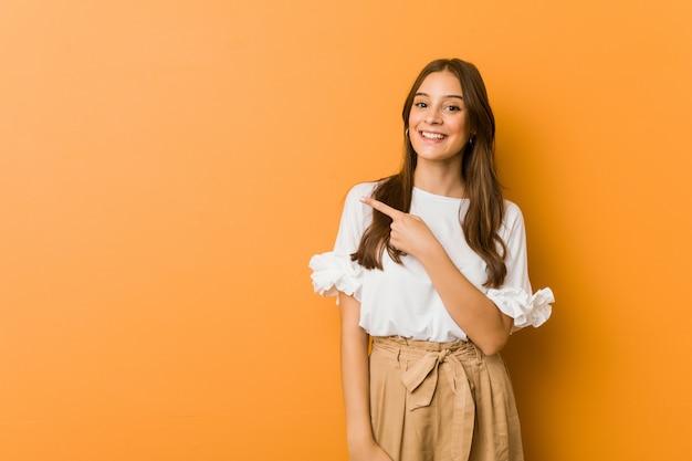 Jovem mulher caucasiana, sorrindo e apontando de lado, mostrando algo no espaço em branco. Foto Premium