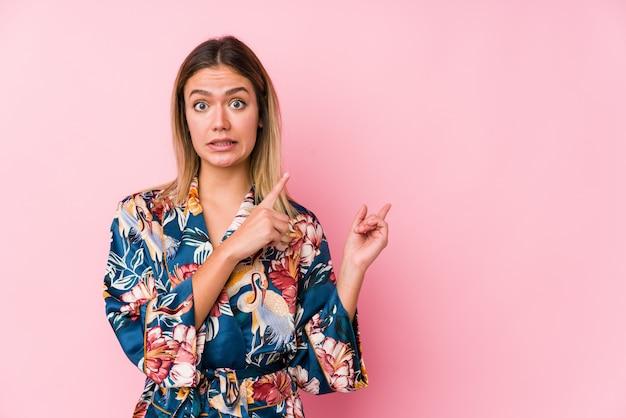 Jovem mulher caucasiana, vestindo pijama chocado apontando com o dedo indicador para um espaço de cópia Foto Premium