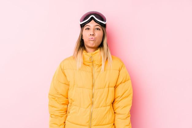 Jovem mulher caucasiana, vestindo uma roupa de esqui em um fundo rosa sopra bochechas, tem expressão cansada. conceito de expressão facial. Foto Premium