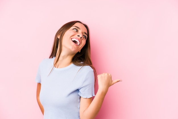 Jovem mulher caucasiana, vestindo uma roupa de esqui pontos isolados com o dedo polegar de distância, rindo e despreocupada. Foto Premium