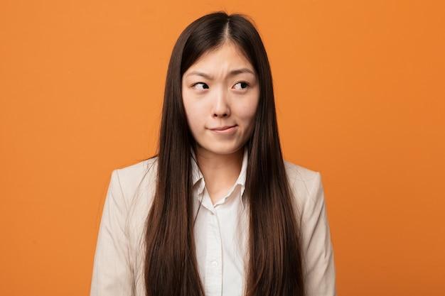 Jovem mulher chinesa de negócios confuso, sente-se duvidosa e insegura. Foto Premium