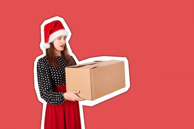 Jovem mulher chocada e surpreendida que prende a caixa de presente grande da caixa. estilo de colagem de revista Foto Premium