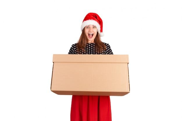 Jovem mulher chocada e surpreendida que prende a caixa de presente grande da caixa. isolado Foto Premium
