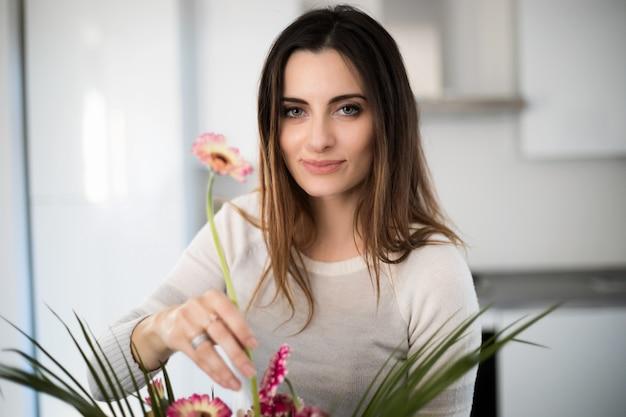 Jovem mulher colocando flores coloridas em vaso Foto Premium
