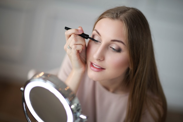 Jovem mulher colocando maquiagem. Foto gratuita