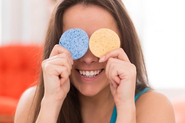 Jovem mulher com almofadas cosméticas Foto gratuita