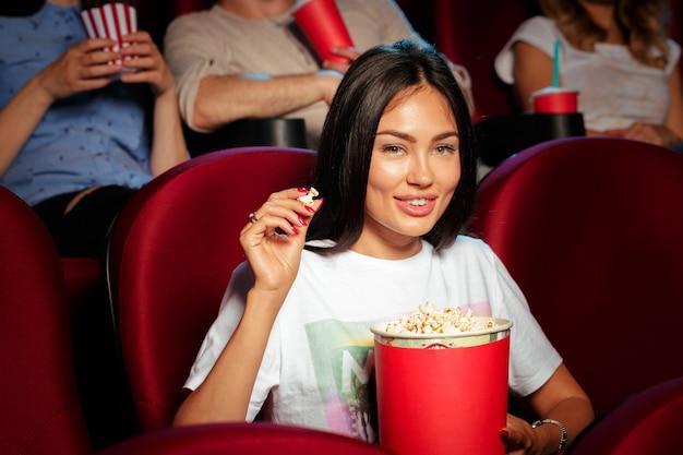 Jovem mulher com amigos assistindo filme no cinema Foto Premium