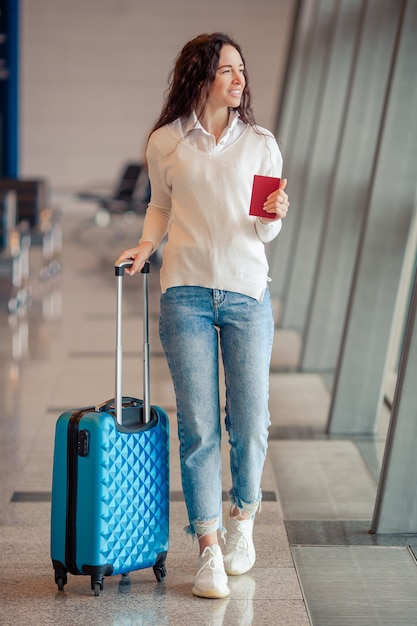 Jovem mulher com bagagem no aeroporto internacional. passageiros de avião em um saguão do aeroporto esperando o avião do voo Foto Premium
