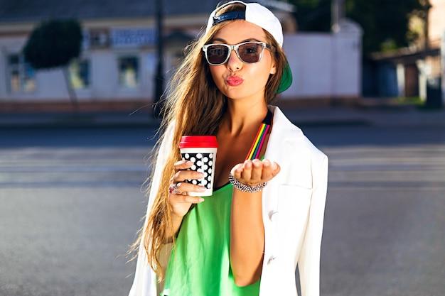 Jovem mulher com boné e óculos de sol bebendo café jogando um beijo na rua Foto gratuita