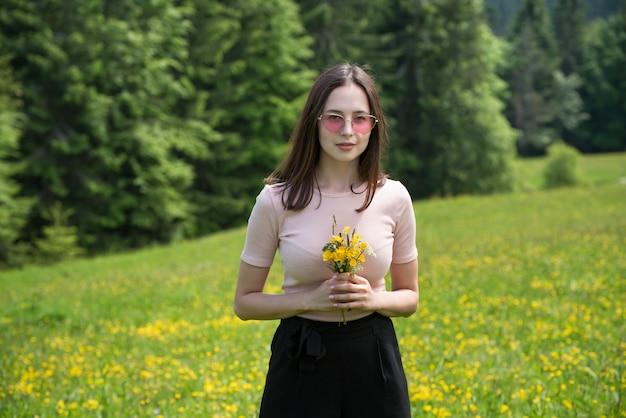 Jovem mulher com buquê de flores silvestres em um gramado ensolarado. Foto Premium