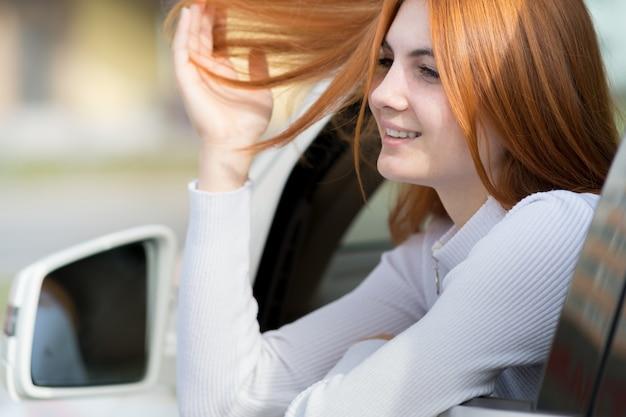 Jovem mulher com cabelo vermelho, dirigindo um carro. Foto Premium