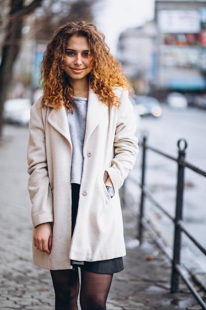 Jovem mulher com cabelos cacheados fora da rua Foto gratuita