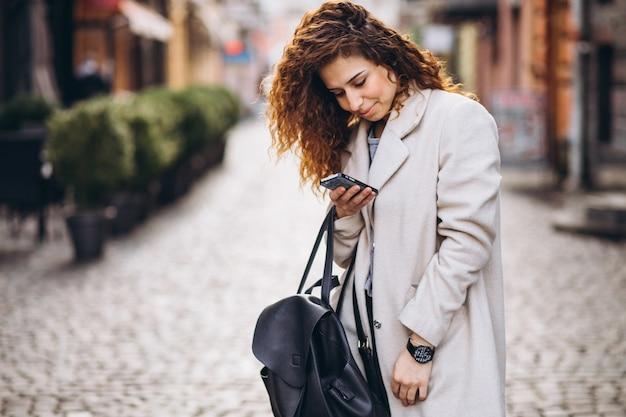 Jovem mulher com cabelos cacheados, usando o telefone na rua Foto gratuita