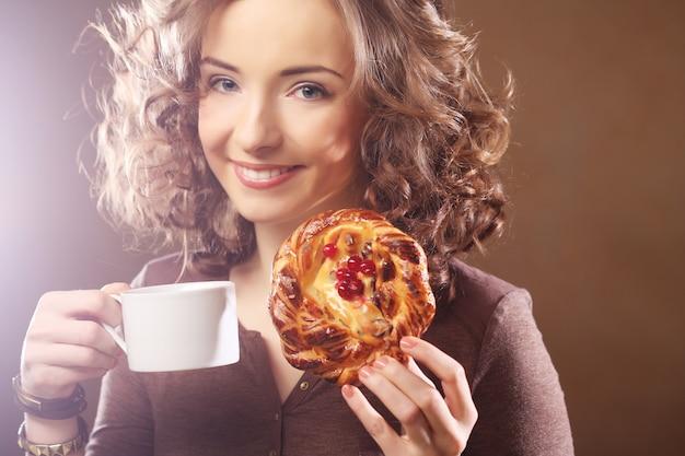 Jovem mulher com café e bolo Foto Premium