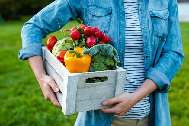 Jovem mulher com caixa de legumes ecológicos frescos ao pôr do sol Foto Premium