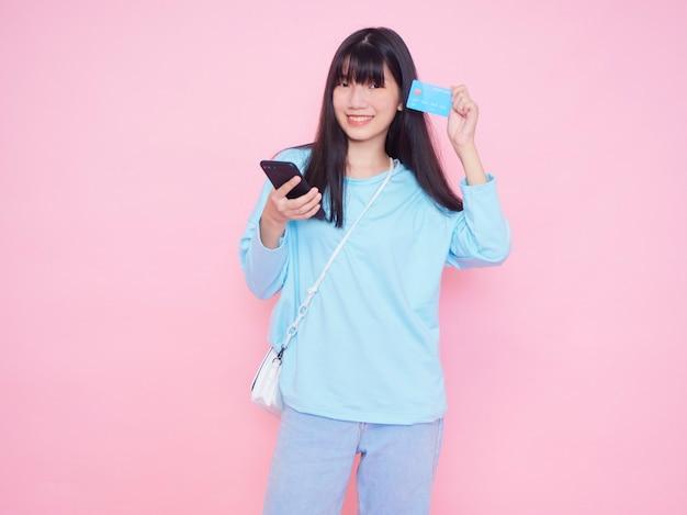 Jovem mulher com cartão de crédito e smartphone na parede rosa. compras online Foto Premium