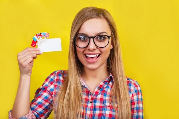 Jovem mulher com cartão e bandeiras de diferentes países de língua. Foto Premium
