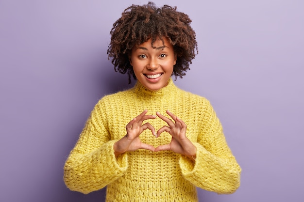 Jovem mulher com corte de cabelo afro e suéter amarelo Foto gratuita