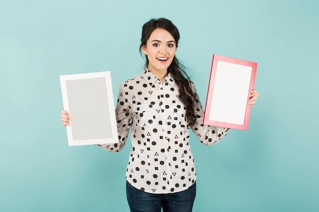 Jovem mulher com dois quadros em branco Foto Premium