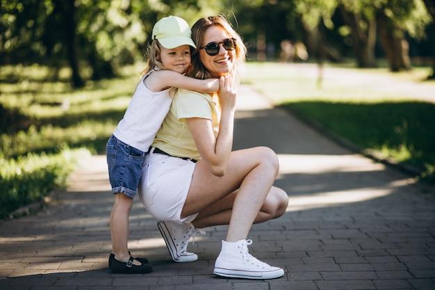Jovem mulher com filha caminhando no parque Foto gratuita
