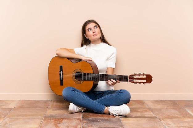 Jovem mulher com guitarra, sentada no chão, rindo e olhando para cima Foto Premium