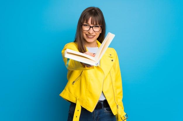 Jovem mulher com jaqueta amarela, segurando um livro e dando a alguém Foto Premium