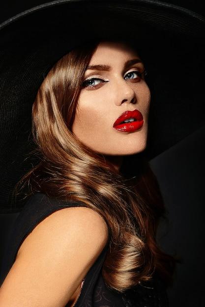 Jovem mulher com lábios vermelhos e chapéu preto Foto gratuita