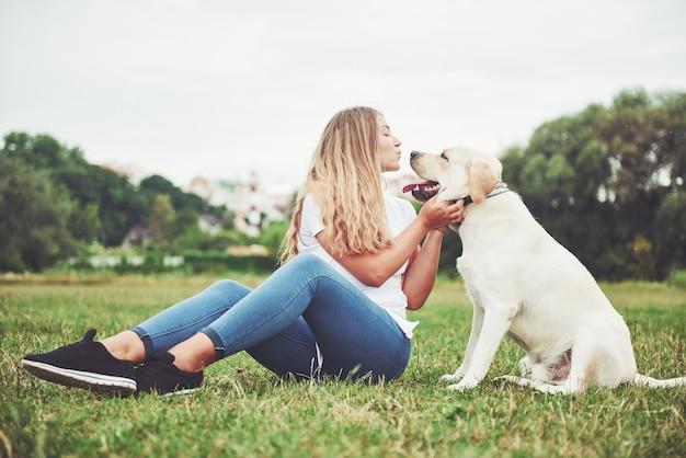 Jovem mulher com labrador ao ar livre. mulher em uma grama verde com cachorro labrador retriever. Foto gratuita