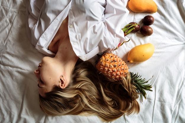 Jovem mulher com longos cabelos loiros, deitada na cama Foto Premium